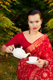 Woman in Indian sari with teapot and cup of tea. Beautiful woman in Indian red sari with teapot pouring tea into the cup outdoors in autumn time Royalty Free Stock Photo