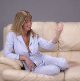 Woman indicating with her finger to come closer. Woman wearing pjyamas laying on a sofa indicating with her finger to advance or come closer Stock Photos