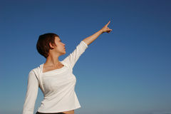 Woman indicating the sky. Woman showing the blue sky Stock Photography