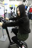 Woman in Indoor bycicle cycling in gym. Competition, caucasian. Woman people spinning in the gym, exercising their legs doing cardio training at shanghai Stock Image