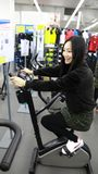 Woman in Indoor bycicle cycling in gym. Competition, caucasian. stock images