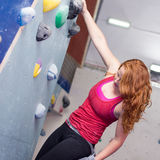 Woman Indoor Free Climbing. Young redhead woman free climbing at indoor climbing wall Stock Photos