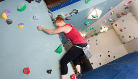 Woman Indoor Free Climbing. Young redhead woman free climbing at indoor climbing wall Royalty Free Stock Photos