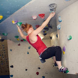 Woman Indoor Free Climbing. Young redhead woman free climbing at indoor climbing wall Stock Photo