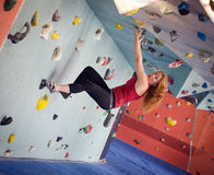 Woman Indoor Free Climbing. Young redhead woman free climbing at indoor climbing wall Stock Photography