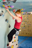 Woman Indoor Free Climbing. Young redhead woman free climbing at indoor climbing wall Royalty Free Stock Image