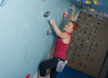 Woman Indoor Free Climbing. Young redhead woman free climbing at indoor climbing wall Stock Images