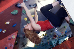 Woman Indoor Free Climbing. Young redhead woman free climbing at indoor climbing wall Royalty Free Stock Photo
