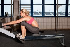Woman On Indoor Rowing Machine. Young fit woman rowing indoor on a rowing machine Stock Image