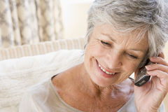 Woman indoors using cellular phone Stock Images