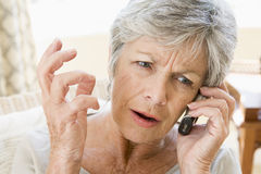 Woman indoors using cellular phone frowning.  Royalty Free Stock Images