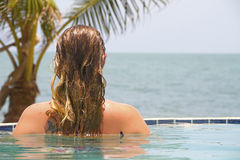 Woman in an infinity pool beside ocean Royalty Free Stock Image