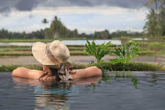 Woman in infinity pool with rice fields view Royalty Free Stock Images