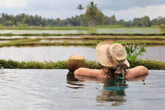 Woman in infinity pool with rice fields view Royalty Free Stock Photography