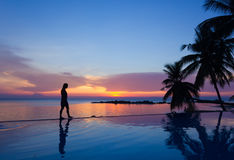 Woman on infinity pool. Woman silhouette walking over infinity pool at sunset in Koh Phangan, Thailand Royalty Free Stock Photos