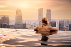 Woman in infinity swimming pool. Business district aerial view. Downtown landscape at golden sunset in Marina Bay royalty free stock photography