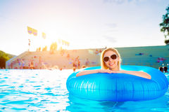 Woman in inflatable ring in pool. Sunny summer and water. Royalty Free Stock Photo