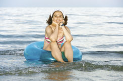 Woman with an inflatable rubber ring. Woman sitting in an inflatable rubber ring in the sea Royalty Free Stock Images