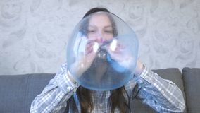 Woman inflates a big bubble from a blue slime. Play with slime. Woman inflates a big bubble from a blue slime stock video
