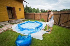 Woman inflates inflatable swimming pool. In the yard of a country house stock images