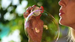 Woman inflates soap bubbles. Slow motion stock video footage