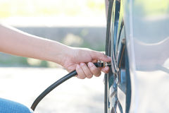 Woman inflating car tire. Close up,woman checking pressure and inflating car tire Stock Photo