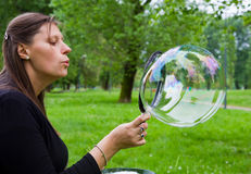 Woman inflating colorful soap bubbles in spring park Royalty Free Stock Images