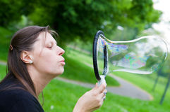Woman inflating colorful soap bubbles in spring park Stock Photos