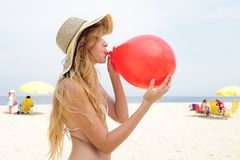 Woman inflating a red balloon on the beach. Party prewoman inflating a red balloon on the beach Royalty Free Stock Photos