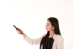 Woman with an infrared remote control pointing it at the viewer Royalty Free Stock Image