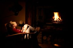 Woman infront of the fire. Blonde woman sitting infront of the fireplace, reading the book and thinking royalty free stock photo