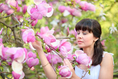 Woman inhaling aroma of spring flowers in the garden Stock Photos