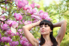 Woman inhaling aroma of spring flowers in the garden Royalty Free Stock Photography
