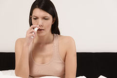 Woman inhaling nose drops Stock Images