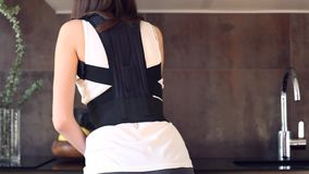 Woman with injured back wears back support bandage