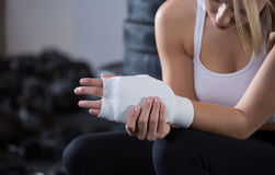 Woman with injured wrist. At the gym stock photos