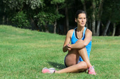 Woman Injury Prevention. Young female athlete stretching buttocks and holding leg for injury prevention sitting on grass in a park Stock Photography