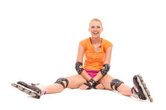 Woman on inline skates sitting and resting. Stock Images