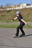 Woman Inline Skating - Leisure Activity. Inline Skating woman with helmet, black clothes and sun glasses royalty free stock photo