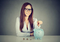 Woman inserting coin in a piggy bank stock photos