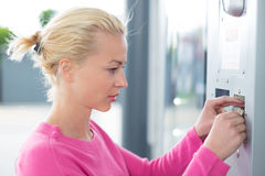 Woman inserting coin in the vending machine. Royalty Free Stock Photos
