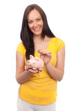 Woman inserting coins in a piggy bank. Attractive young woman inserting coins in a piggy bank on white background Royalty Free Stock Photos
