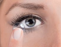 Woman inserting a contact lens. Closeup of a woman inserting a contact lens Royalty Free Stock Photo
