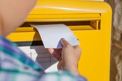 Woman inserting envelope in mailbox Royalty Free Stock Images