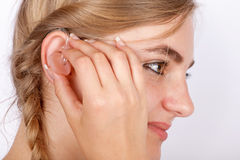 Woman inserting a hearing aid into ear royalty free stock photo