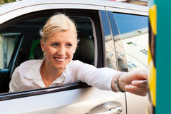 Woman is inserting parking ticket into barrier Stock Image