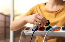 Woman inserting power plug into extension cord indoors. Electrician`s professional equipment stock photos