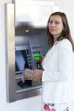Woman inserts card in the ATM Stock Photo
