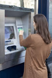 Woman putting card into ATM Royalty Free Stock Photos
