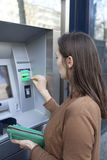 Woman putting card into ATM in spring Royalty Free Stock Photos